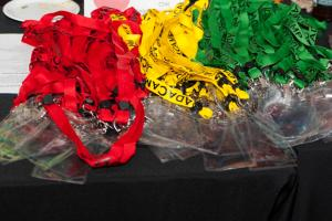 Three piles of coloured lanyards, red, yellow, and green
